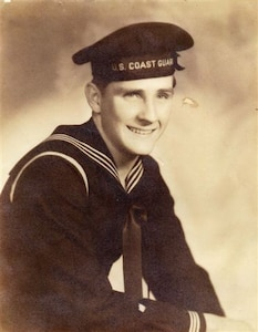 "Coast Guardsman Marvin Perret, USCGR, in dress blues: this uniform was the same as worn by Navy sailors except for the shield device, in white, on the lower right sleeve which denoted Coast Guard personnel and the cap ribbon which had ""U.S. Coast Guard"" stitched on it instead of ""U.S. Navy"", WWII."