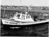 "CG-40428: next to the Coast Guard ensign is BM3 (later BMCM) Charles ""Mac"" McGowan, alongside him is EN2 Reagan, third crewman is unknown."