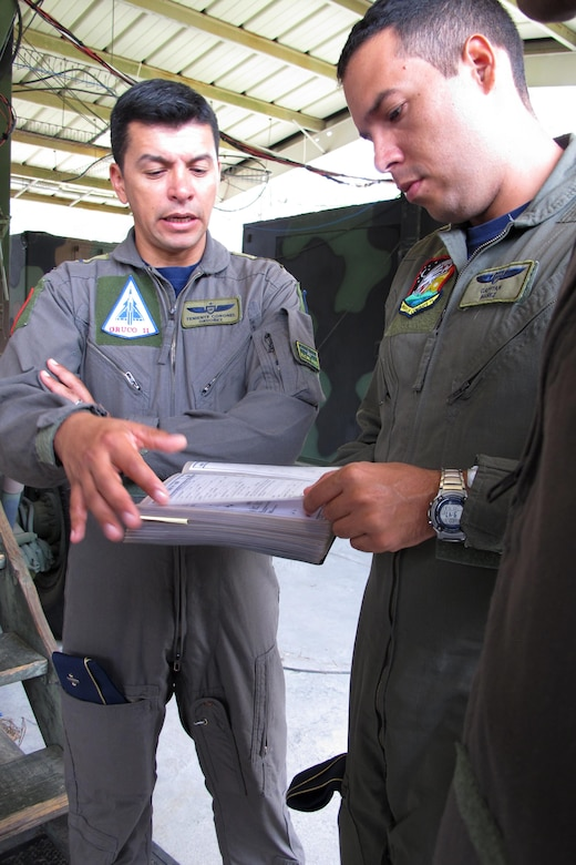 Colombian Air Force Lt. Col. Jorge Ordonez (left) and Colombian Air Force Capt, Rodrigo Nunez look over Ground Control Intercept training manuals at the Georgia Air National Guard 117th Air Control Squadron at Hunter Army Airfield in Savannah, Georgia May 30-June 2, 2017 during a State Partnership Program engagement with the South Carolina National Guard. (U.S. Air National Guard photo by Capt. Stephen D. Hudson)