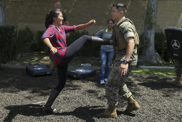 U. S. Marine Corps Capt. Geoffrey Irving, legal assistant attorney, and his wife, Anna Chou, practice their Marine Corps Martial Arts techniques during J. Wayne Day on Camp Pendleton, Calif., April 28, 2017. J. Wayne Day is an event hespouses or loved ones have a chance to participate in multiple activities such as the Marine Corps Martial Arts, Pistol Range and the Fire Crash and Rescue followed by various demonstrations and displays. (U. S. Marine Corps photo by Lance Cpl. Betzabeth Y. Galvan)