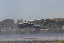U.S. Navy Seahawk 60 helicopter lowers it's bambi bucket to collect lake water during the 2017 Wildland Firefighting Exercise (WLFFEX) at Lake O'Neill on Camp Pendleton, Calif., May 4, 2017. The WLFFEX is an annual training event to exercise the firefighting efforts by aviation and ground assests from Marine Corps Installations - West, Marine Corps Base, Camp Pendleton, 3rd Marine Aircraft Wing, Navy Region South West, Third Fleet, CAL FIRE, and San Diego County Sheriff's Department. (U.S. Marine Corps photo by Cpl. Brandon Martinez)