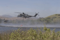 U.S. Marine Corps CH-53E Super Stallion lowers its bambi bucket to collect water during the 2017 Wildland Firefighting Exercise (WLFFEX) at Lake O'Neil on Camp Pendleton, Calif., May 4, 2017. The WLFFEX is an annual training event to exercise the firefighting efforts by aviation and ground assests from Marine Corps Installations - West, Marine Corps Base, Camp Pendleton, 3rd Marine Aircraft Wing, Navy Region South West, Third Fleet, CAL FIRE, and San Diego County Sheriff's Department. (U.S. Marine Corps photo by Cpl. Brandon Martinez)