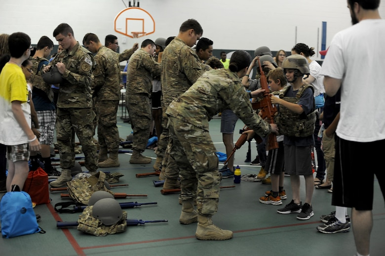 Members from the 791st Missile Security Forces Squadron convoy response force help children gear up at Operation Heroes at Minot Air Force Base, N.D., June 3, 2017. Operation Heroes is an annual event that also included gear to try on, different weapons displays and a deployment line. (U.S. Air Force Photo by Staff Sgt. Chad Trujillo)