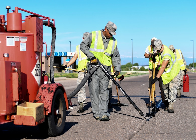 Chief Master Sgt. Rod Lindsey, 460th Space Wing command chief, fills holes and cracks in roads on base with the 460th Civil Engineer Squadron Dirt Boyz June 8, 2017 on Buckley Air Force Base, Colo. One of Lindsey's initiatives as command chief is experiencing the jobs of Team Buckley Airmen first hand. (U.S. Air Force photo by Staff Sgt. Andrew Helmkamp/ Released)