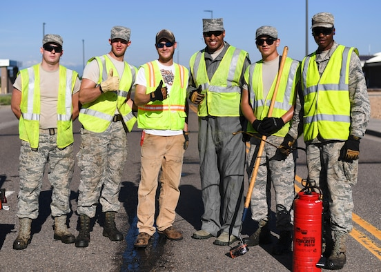 Chief Master Sgt. Rod Lindsey, 460th Space Wing command chief, poses with the 460th Civil Engineer Squadron Dirtboyz after spending their morning filling cracks in the roads June 8, 2017 on Buckley Air Force Base, Colo. One of Lindsey's initiatives as command chief is experiencing the jobs of Team Buckley Airmen first hand. (U.S. Air Force photo by Staff Sgt. Andrew Helmkamp/ Released)