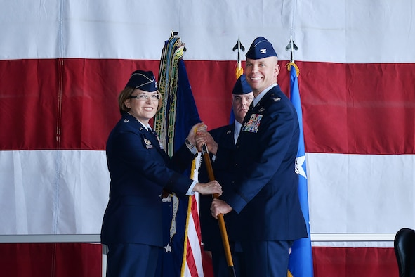 Maj. Gen. Mary F. O'Brien, 25th Air Force commander, presents Col. Michael Manion with the 55th Wing guidon during a chang of command ceremony in Dock 1 of the Bennie Davis Maintenance Facility June 8. The Fightin' Fifty-Fifth said farewell to Col. Marty Reynolds and welcomed Col. Manion.