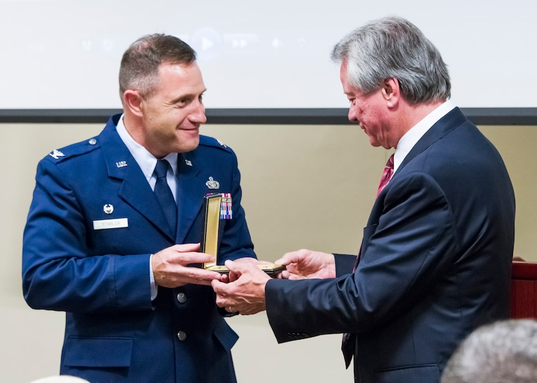 Col. Kirk B. Stabler, Air Force Office of Special Investigations Commander, presents the Bronze Star Medal of Fallen Special Agent Lee Hitchcock to his brother, Mr. Craig Hitchcock, during the OSI headquarters inaugural Celebration of Life Remembrance Ceremony May 22, 2017, at Quantico, Va. (U.S. Air Force photo/Mr. Michael Hastings)