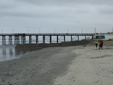 Manson Construction Company places material dredged from the Oceanside Harbor entrance channel along the beach just south of the Oceanside Pier. The contractor expects to complete the dredging of up to 425,000 cubic of sand from the channel by the night of Monday, June 12, if not before.