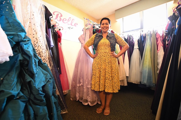 Angy Hogan poses with dresses at Hill Air Force Base, June 8. Hogan coordinates the 'Belle of the Ball' loan closet, a program that provides, free of charge, formal and semi-formal wear to active duty, retirees and their dependents so that they may have something beautiful to wear for special occasions. She is the spouse of active duty Tech. Sgt. Thomas Hogan, Air Force Nuclear Weapons Center, and was recently named 2017 Armed Forces Insurance Military Spouse of the Year for Hill AFB.  (U.S. Air Force/R. Nial Bradshaw)