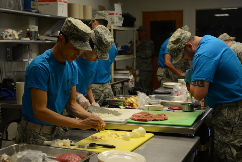 Airmen from the 341st Force Support Squadron work as teams of two to prepare meals from scratch during the Warrior Chef competition June 7, 2017 at Malmstrom Air Force Base, Mont. Each teams' dishes were scored on taste, texture, tenderness, creativity, presentation and use of the secret ingredient. (U.S. Air Force photo/Staff Sgt. Delia Marchick)