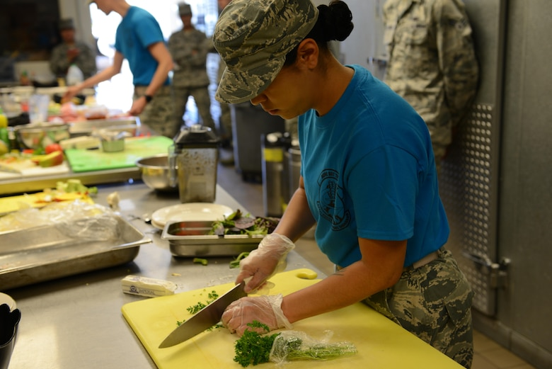 Staff Sgt. Amber Sansone, 341st Force Support Squadron missile chef, cuts parsley during the Warrior Chef competition June 7, 2017 at Malmstrom Air Force Base, Mont. Sansone and Airman 1st Class Nicki Agunos, 341st FSS missile chef, worked on the same team and won the competition. (U.S. Air Force photo/Staff Sgt. Delia Marchick)