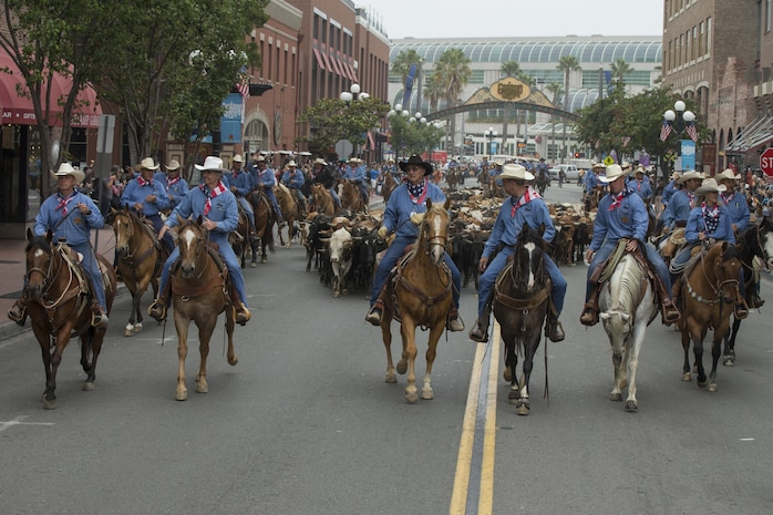U.S. Marine Corps Brig. Gen. Kevin J. Killea, Marine Corps Installations West, Marine Corps Base, Camp Pendleton, and members of the San Diego County fair participate in a cattle drive throughGas Lamp District in San Diego, Calif., June 3, 2017. The San Diego County Fair hosted the drive as a part of the gas lamp district's 150th anniversary and to promote the county fair that opened June 2. (U.S. Marine Corps photo by Lance Cpl. Brooke Woods)
