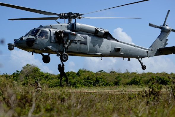 A U.S. Airman from the 9th Expeditionary Bomb Squadron descends from a U.S. Navy MH-60 Seahawk, assigned to Helicopter Sea Combat Squadron Two-Five, during a combat search and rescue training exercise June 5, 2017, at Andersen South, Guam. Service members from Task Force Talon, HSC-25, and the 36th Wing joined together to practice survival, evasion, resistance and escape procedures, emergency evacuation techniques and quick reaction force training. This is the first time these units participated in a combat search and rescue exercise together on Guam.(U.S. Air Force photo by Airman 1st Class Gerald R. Willis)