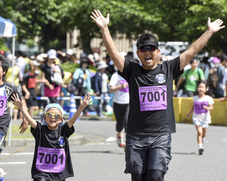 A father and daughter cross the finish line together with their hands up at the 2K Family Run during the 33rd Annual Yokota Striders Ekiden at Yokota Air Base, Japan, June 4, 2017. More than 5,000 runners participated in the event hosted by the Yokota Striders Running Club. (U.S. Air Force photo by Machiko Arita)