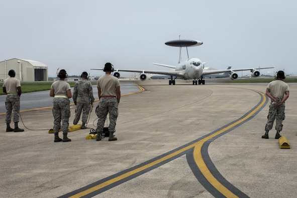 U.S. Air Force crew chiefs and specialists from the 961st Aircraft Maintenance Unit prepare to recover an approaching E-3 Sentry from the 961st Airborne Air Control Squadron June 8, 2017, at Kadena Air Base, Japan. To prepare the aircraft to fly, AMU Airmen perform day-to-day maintenance, specializing in a wide variety of systems such as radio, navigation, radar, coolant and computer systems. (U.S. Air Force photo by Senior Airman John Linzmeier)