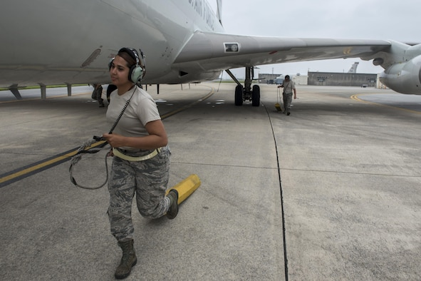 U.S. Air Force Airman 1st Class Erika Jimenez, 961st Aircraft Maintenance Unit aerospace propulsion technician, pulls away an aircraft wheel chock from an E-3 Sentry from the 961st Airborne Air Control Squadron June 8, 2017, at Kadena Air Base, Japan. In support of air-to-ground operations, the Sentry can provide direct information needed for interdiction, reconnaissance, airlift and close-air support for friendly ground forces. (U.S. Air Force photo by Senior Airman John Linzmeier)