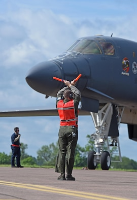 U.S. Air Force Airman 1st Class Jacob Feeback, 28th Aircraft Maintenance Squadron crew chief, marshals a B-1B Lancer assigned to Ellsworth Air Force Base, S.D. at RAF Fairford, U.K., June 7, 2017. Bomber missions in the European theatre enable crews to maintain a high state of readiness and proficiency, and validate the Air Force's always-ready global strike capability. (U.S. Air Force photo by Tech. Sgt. Miguel Lara III)