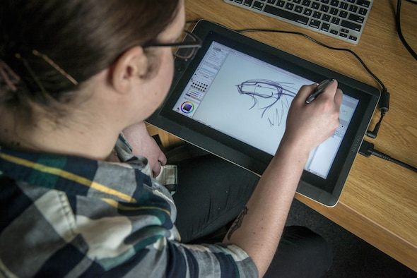 """U.S. Air Force Airman 1st Class Kelly Coats, a 35th Operations Support Squadron airfield manager, sketches a dragon in her dorm room for fun at Misawa Air Base, Japan, May 23, 2017. Coats draws anything form dragons to knights in shining armor to the base's comic strip, """"Airmanitis."""" She said drawing is what gets her up in the morning and what relaxes her at the end of the day—it's how she maintains her resiliency as a warfighter. (U.S. Air Force photo by Tech. Sgt. Benjamin W. Stratton)"""