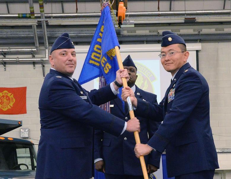 U.S. Air Force Col. Robert Hoskins, left, 100th Mission Support Group commander, passes the guidon to U.S. Air Force Maj. Robert Liu, new 100th Civil Engineer Squadron commander, June 6, 2017, during a change of command ceremony on RAF Mildenhall, England. The ceremony is a time-honored tradition in which one officer relinquishes command and passes it to another. (U.S. Air Force photo by Karen Abeyasekere)