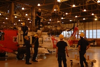 """Air Station Kodiak, Alaska Original photo caption: """"Crewmen from Coast Guard Air Station Kodiak remove the main rotor head from an HH-60 Jayhawk helicopter during maintenance Monday.  The main rotor head is routinely inspected for wear and tear every 800 flight hours.""""; photo dated 12 December 2005; Photo No. 051212-C-0368R-001 (FR); photo by PA1 Paul Rozkowski, USCG"""