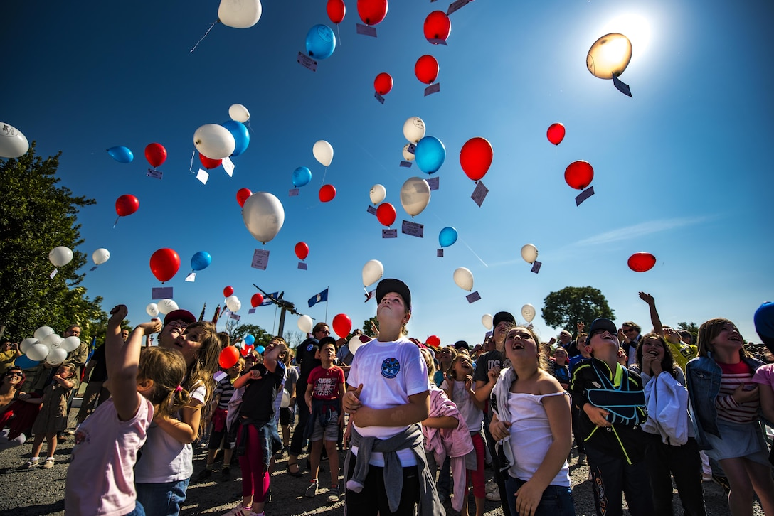 French children release balloons into the air during a D-Day remembrance ceremony at the United States Army Air Forces Transport Memorial in Picauville, France, June 1, 2017. Each balloon had a placard tied to it with the name of a fallen service member who gave their life for the liberation of France. This event commemorates the 73rd anniversary of D-Day, the largest multinational amphibious landing and operational military airdrop in history, and highlights the U.S.' steadfast commitment to European allies and partners. Overall, approximately 400 U.S. service members from units in Europe and the U.S. participated in ceremonial D-Day 73 events from May 31-June 7, 2017. (U.S. Air Force photo/Senior Airman Devin Boyer)
