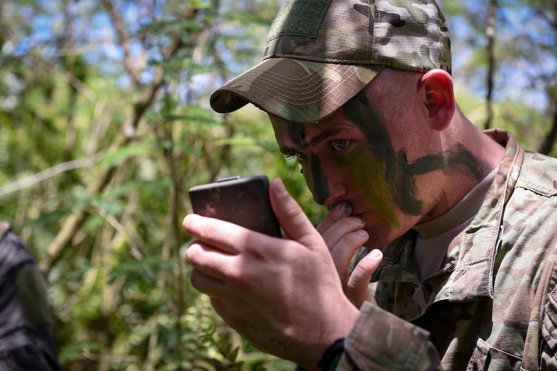 Tech. Sgt. Ryan Hyslop, an Air Force Global Strike Command Detachment 4 survival, evasion, resistance and escape specialist, applies camouflage face paint during a combat search and rescue training exercise June 5, 2017, at Andersen Air Force Base, Guam. During the exercise, Hyslop conducted refresher training for aircrews on how to survive in a jungle environment, evade opposing forces and safely evacuate on a MH-60 Seahawk. (U.S. Air Force photo/Staff Sgt. Joshua Smoot)