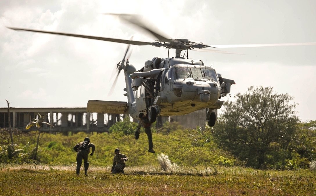 An Airman assigned to the 9th Expeditionary Bomb Squadron descends from a Navy MH-60 Seahawk, assigned to Helicopter Sea Combat Squadron Two-Five, during a combat search and rescue training exercise June 5, 2017, at Andersen Air Force Base, Guam. Service members from Task Force Talon, HSC-25, and the 36th Wing joined together to practice survival, evasion, resistance and escape procedures, emergency evacuation techniques and quick reaction force training. This is the first time units from the Air Force, Navy and Army participated in a combat search and rescue exercise on Guam. (U.S. Air Force photo/Staff Sgt. Joshua Smoot)