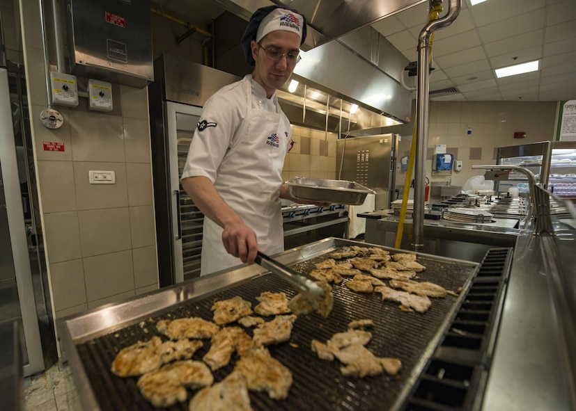Airman Nathaniel Johnson, 31st Force Support Squadron food service apprentice, grills fresh chicken for lunch May 26, 2017, at Aviano Air Base, Italy. The La Dolce Vita, Aviano AB dining facility, has recently made improvements to provide healthier options and enhance the quality of food for Airmen and Soldiers. (U.S. Air Force photo by Senior Airman Cory W. Bush)