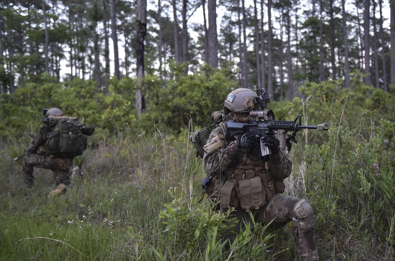 A U.S. Air Force Special Tactics officer with the 24th Special Operations Wing provides rear security during a troop movement at Field Training Exercise Raider Spirit, May 1, 2017, at Camp Lejeune, N.C. For the first time, Special Tactics Airmen spent three months in Marine Special Operations Command's Marine Raider training pipeline, representing efforts to build joint mindsets across special operations forces.  (U.S. Air Force photo by Senior Airman Ryan Conroy)