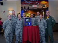 """U.S. Air Force Col. Mark Ely, far right, the 509th Bomb Wing vice commander, gathers with members of Team Whiteman around a display featuring Trinitite at Whiteman Air Force Base, Mo., June 2, 2017. Trinity Site is where the first atomic bomb was tested on July 16, 1945. With a power equivalent to around 21,000 tons of TNT, the bomb completely obliterated the steel tower on which it rested. The intense heat melted the New Mexico desert sand into a light green, glass-like substance which was later named """"Trinitite."""" (U.S. Air Force photo by Airman 1st Class Jazmin Smith)"""