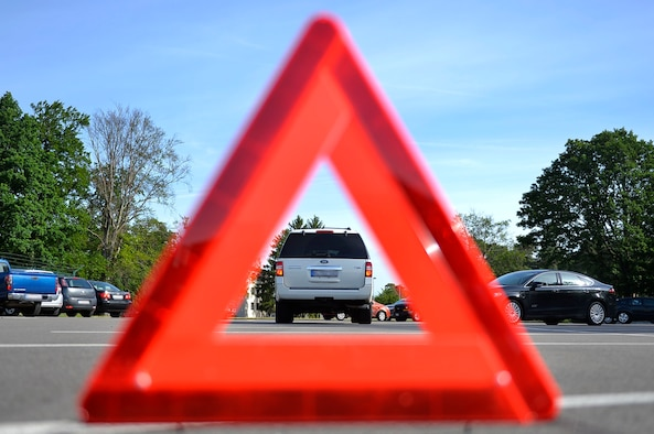 A hazard triangle stands behind a parked vehicle at Ramstein Air Base, Germany, June 8, 2017. Motorists in Germany are required to keep a first aid kit, reflective vests and a hazard triangle in their vehicle. (U.S. Air Force photo illustration by Airman 1st Class Joshua Magbanua)