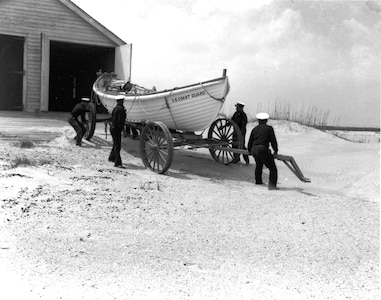 """Station Pea Island, North Carolina USLSS Station #17, Sixth District Coast Guard Station #177 Coast Guard Lifeboat Station Pea Island Crew   Official caption reads: """"Coast Guard crew making ready their surfboat at the all-Negro Coast Guard Lifeboat Station at Pea Island, N.C."""" No date/photo number; photographer unknown.  Probably 1942."""