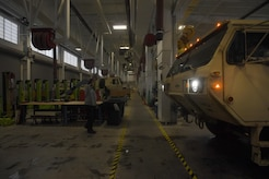 Machinists and automotive mechanics at the Army Support Activity Logistics Readiness Center escort a vehicle in an engineering bay at Joint Base McGuire-Dix-Lakehurst, New Jersey, June 7, 2017. The 38 active engineering bays see vehicles ranging from small all-terrain-vehicles from the 621st Contingency Response Wing to large vehicles able to carry a 60-ton tank.