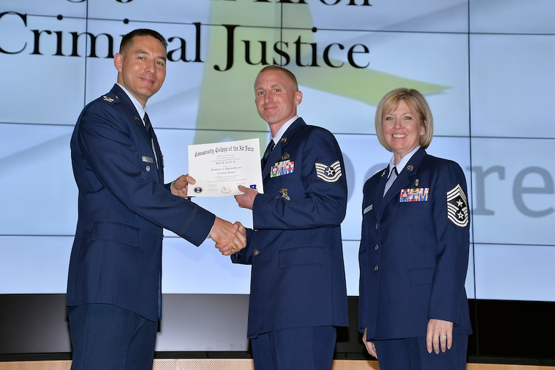 Tech. Sgt. John Kroll (center), 10th Security Forces Squadron, receives his Community College of the Air Force degree from Col. Patrick Carley, 10th Air Base Wing vice commander, June 6, 2017, at the Community College of the Air Force graduation ceremony at the U.S. Air Force Academy. Chief Master Sgt. Lisa Buckman, 10th ABW command chief is on the right. In all, 38 Airmen received CCAFs diplomas or professional certificates at the graduation ceremony in Polaris Hall. (U.S. Air Force photo/Darcie Ibidapo)