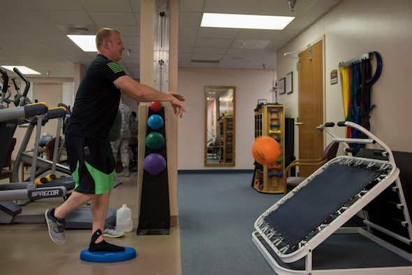 Casey Wheat, physical therapy patient, throws a medicine ball while balancing at the 27th Special Operations Medical Group Physical Medicine Office April 26, 2017, at Cannon Air Force Base, NM. On average, physical therapy sees 40 patients a day, most of which are repeat clients. Usually a patient will come in two or three times a week for one or two months. (U.S. Air Force photo by Staff Sgt. Michael Washburn/Released)