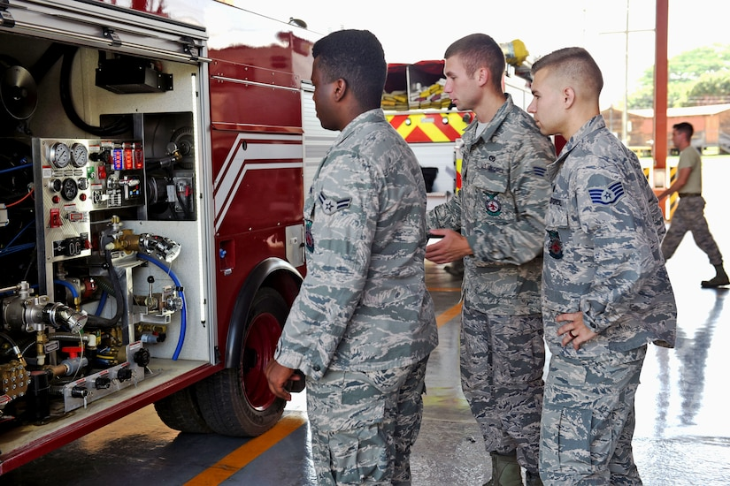 U.S. Air Force Staff Sergeant Zachary White (far right), 612th Air Base Squadron, shows Airman 1st Class Eric Van (left) and Senior Airman Eli Blue (center) how to properly check the Fire Department vehicles at Soto Cano Air Base, May 25th, 2017, to prevent any delays when exiting the Fire Department in response to a fire. Staff Sgt. White works as a Fire crew chief at Joint Task Force-Bravo's Fire Emergency Services and is in charge of a four member team prepared to respond to an emergency situation on base.  (U.S. Army photo by Maria Pinel)