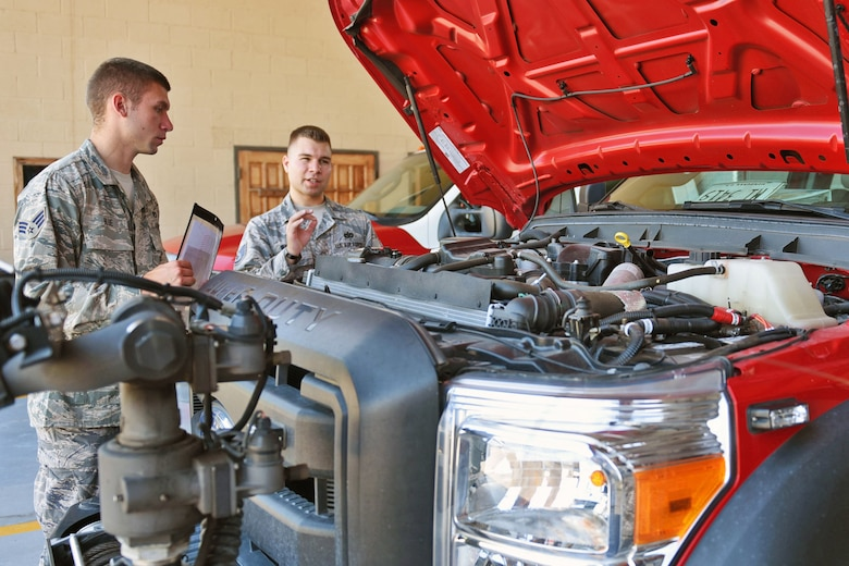 U.S. Air Force Staff Sergeant Zachary White (right), 612th Air Base Squadron, Fire Emergency Services crew chief, shows Senior Airman Eli Blue (left) how to properly check the Fire Department vehicles at Soto Cano Air Base, May 25th, 2017. Staff Sgt. White works as a Fire crew chief at Joint Task Force-Bravo's Fire Emergency Services and strives to make his team progress professionally and perform their jobs as best they can.  (U.S. Army photo by Maria Pinel)