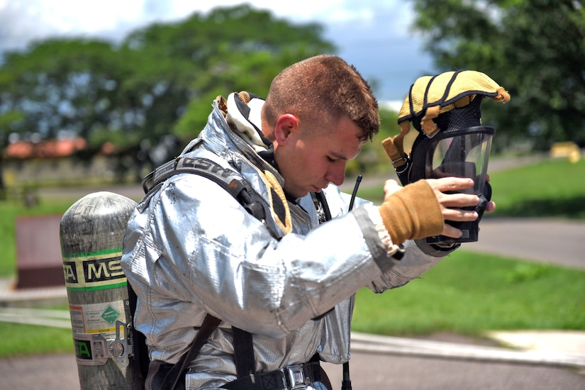 U.S. Air Force Staff Sergeant Zachary White, 612th Air Base Squadron, Fire Emergency Services crew chief, removes his protective gear during a simulated call to action exercise in response to a fire emergency at Soto Cano Air Base, May 25th, 2017. White works as a Fire crew chief at Joint Task Force-Bravo's Fire Emergency Services with a team of four members and strives to make them perform their jobs the as best they can.  (U.S. Army photo by Maria Pinel)