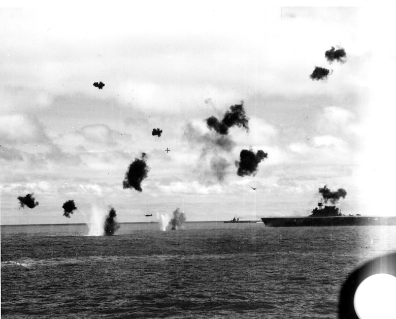 Two Type 97 shipboard attack aircraft from the Japanese carrier Hiryu fly past USS Yorktown (CV-5), amid heavy anti-aircraft fire, after dropping their torpedoes during the mid-afternoon attack, 4 June 1942. Yorktown appears to be heeling slightly to port, and may have already been hit by one torpedo. Photographed from USS Pensacola (CA-24). The destroyer at left, just beyond Yorktown's bow, is probably USS Morris (DD-417). Official U.S. Navy Photograph, now in the collections of the U.S. National Archives.  Source:  (U.S. Navy)
