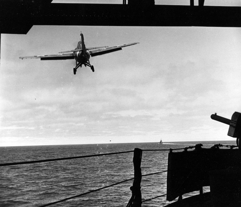 A Grumman F4F-4 Wildcat fighter (Bureau # 5244) takes off from USS Yorktown (CV-5) on combat air patrol, during the morning of 4 June 1942. This plane is Number 13 of Fighting Squadron Three (VF-3), flown by the squadron Executive Officer, Lieutenant (Junior Grade) William N. Leonard. Photographed by Photographer Second Class William G. Roy, from the ship's forecastle. Note .50 caliber machinegun at right and mattresses hung on the lifeline for splinter-protection. Official U.S. Navy Photograph, now in the collections of the National Archives. Source:  (U.S. Navy)
