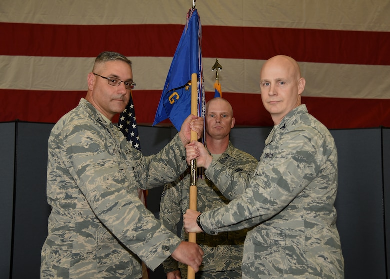 Colonel Stephen Kravitsky, 90th Missile Wing commander, passes the guidon to Col. John Grimm, 90th Security Forces Group commander, during the 90th SFG change of command ceremony June 9, 2017, as Chief Master Sgt. John Facemire, 90th SFG chief enlisted manager, stands in the background in the Peacekeeper High Bay on F.E. Warren Air Force Base, Wyo. The ceremony signified the transition of command from Col. Chris Corley to Grimm. (U.S. Air Force photo by Glenn S. Robertson)