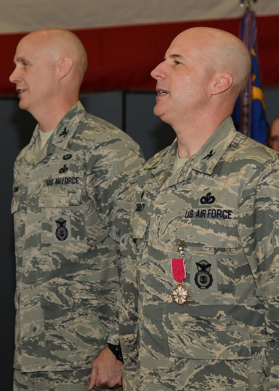 Colonel Chris Corley, outgoing Commander of the 90th Security Forces Group, and Col. John Grimm, sing the Air Force Song at the end of the 90th SFG Change of Command in the Peacekeeper High Bay on F.E. Warren Air Force Base, Wyo., June 9, 2017. Grimm assumed command of the group during the ceremony which represents a formal transition of authority from the outgoing commanding to the incoming commander. (U.S. Air Force photo by Glenn S. Robertson)