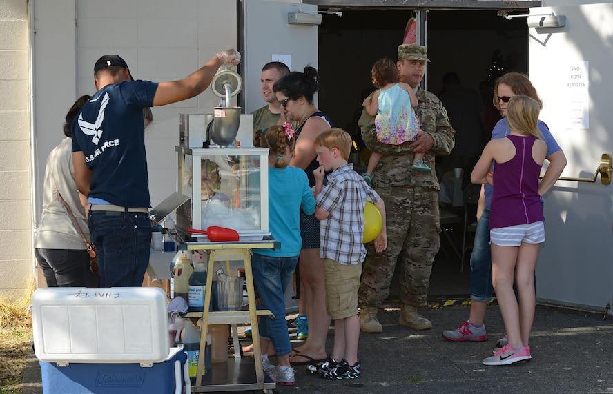 Volunteers from the 627th Logistics Readiness Squadron make snow cones for Airmen and their families at the Hearts Apart dinner June 6, 2017, at Joint Base Lewis-McChord, Wash. The night was Hawaiian-themed, and more than 30 Airmen and their families were provided a free, catered meal served by leadership. (U. S. Air Force photo/Senior Airman Jacob Jimenez)