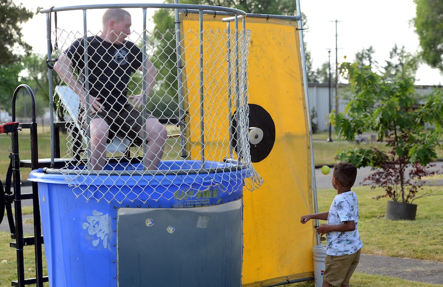 A McChord Field dependent dunks Senior Master Sgt. James Niblock, 627th Logistics Readiness Squadron deployment and distribution flight superintendent, into a dunk tank at the Hearts Apart dinner June 6, 2017, at Joint Base Lewis-McChord, Wash. The informal dinner allowed Airmen to attend in civilian attire with their spouses and children, and participate in a variety of activities. (U.S. Air Force photo/Senior Airman Jacob Jimenez)