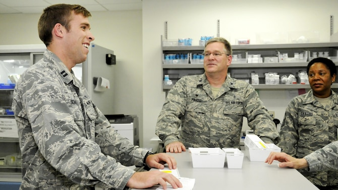 Capt. Michael Schultz, a pharmacist temporarily assigned to the Patient Care Clinic at Hanscom Air Force Base, Mass., welcomes Col. Russell Pinard and Chief Master Sgt. Michelle Castro, commander and superintendent of the 66th Medical Squadron, respectively, to the pharmacy June 7. Pinard and Castro recently took the senior officer and senior enlisted positions with the medical squadron and toured the clinic, familiarizing themselves with the squadron and its Airmen. (U.S. Air Force photo by Benjamin Newell)