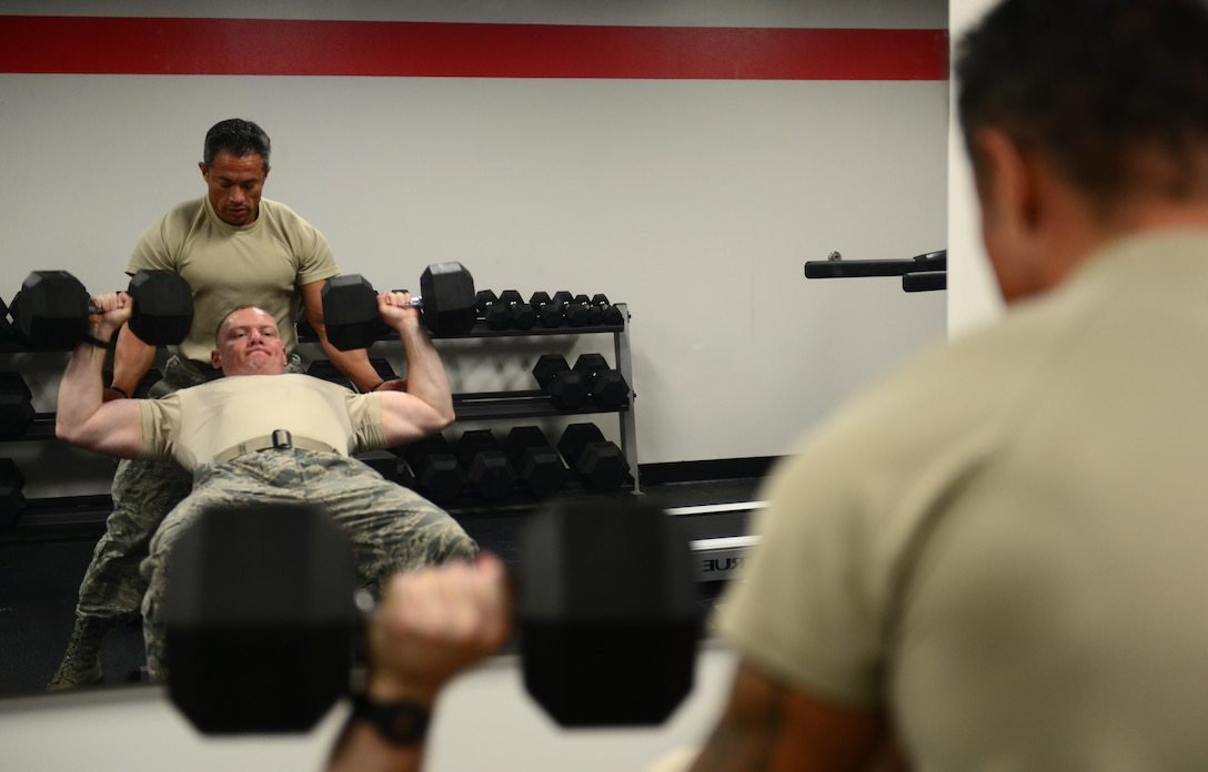 U.S. Air Force Tech. Sgt. Ricardo Zuniga, a weapons load crew member from the 131st Aircraft Maintenance Squadron, spots U.S. Air Force Master Sgt. Jonathon Hamilton, a weapons load crew member from the 131st Aircraft Maintenance Squadron, while he performs dumbbell presses at Whiteman Air Force Base, Mo., May 30, 2017. The flightline gym was recently renovated to benefit flightline personnel wanting to get a workout in without having to leave the flightline. (U.S. Air Force photo by Senior Airman Joel Pfiester)