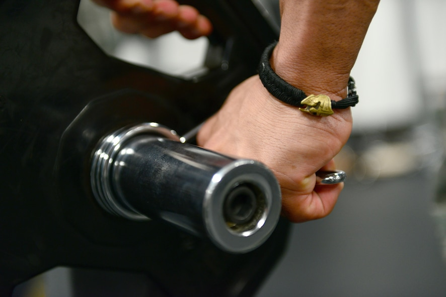 U.S. Air Force Tech Sgt. Ricardo Zuniga, a weapons load crew member from the 131st Aircraft Maintenance Squadron, fastens a clamp on a curl bar while working out at the new flightline gym at Whiteman Air Force Base, Mo., May 30, 2017. The new flightline gym features two treadmills, an elliptical and a row machine, a D-Gym multiuse station, free weights, incline, decline and flat benches, a Smith Machine, and spin bikes. It also features newly mounted fans on the walls, and a sound system equipped with satellite radio. (U.S. Air Force photo by Senior Airman Joel Pfiester)