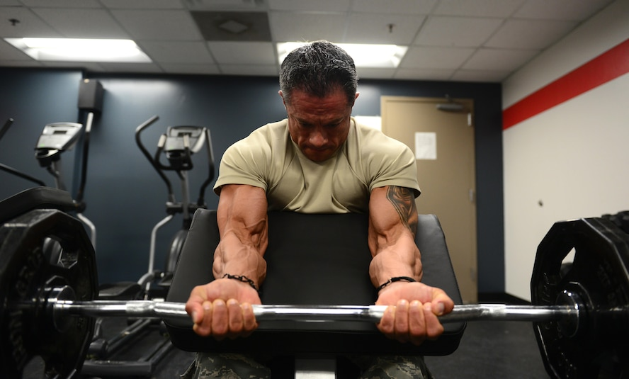 U.S. Air Force Tech. Sgt. Ricardo Zuniga, a weapons load crew member from the 131st Aircraft Maintenance Squadron, performs preacher curls in the new flightline gym at Whiteman Air Force Base, Mo., May 30, 2017. The new flightline gym features two treadmills, an elliptical and a row machine, a D-Gym multiuse station, free weights, incline, decline and flat benches, a Smith Machine, and spin bikes. It also features newly mounted fans on the walls, and a sound system equipped with satellite radio. (U.S. Air Force photo by Senior Airman Joel Pfiester)