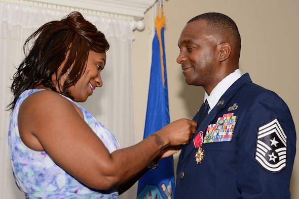 Danya McKinney places a retirement pin on Chief Master Sgt. Christopher McKinney, former 20th Fighter Wing command chief, during his retirement ceremony at Shaw Air Force Base, S.C., June 1, 2017. McKinney enlisted in August 1987 as a weather forecaster, serving in 17 duty positions across the globe including some in support of Operations Joint Endeavor, Iraqi Freedom and Enduring Freedom before becoming the command chief of the 20th FW. (U.S. Air Force photo by Airman 1st Class Kathryn R.C. Reaves)