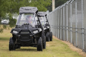 Technical Sgt. Michelle Aberle, 802nd Security Forces Squadron installation security, and Technical Sgt. Paul Turner, 802nd Security Forces Squadron installation security, drive along the base fence line during a security check May 9, 2017, at Joint Base San Antonio-Lackland, Texas.  Aberle and Turner provide force protection for base personnel, equipment and facilities from threats to include intrusion by unauthorized people.